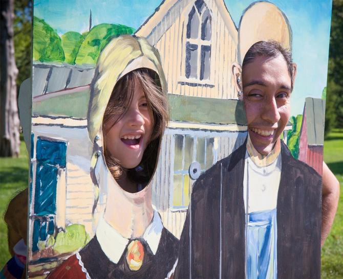 A man and his daughter laugh while putting their faces through cut-out holes in an American Gothic painting at Autumn & Art.