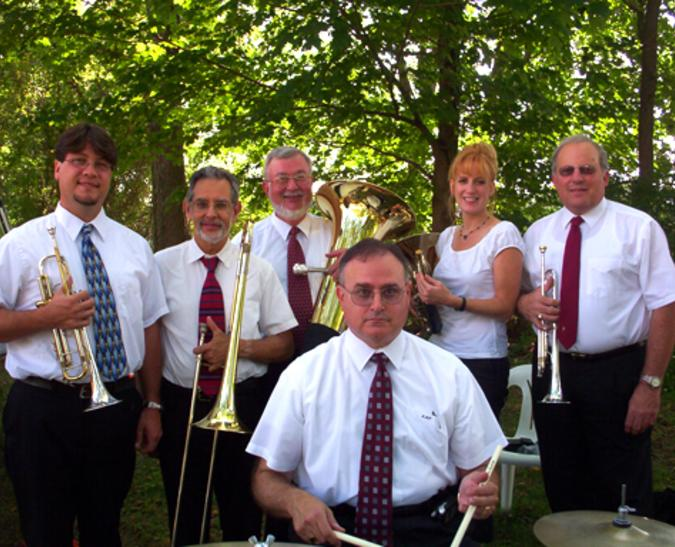 Five men and one woman all in matching white shirts stand together holding their brass instruments.