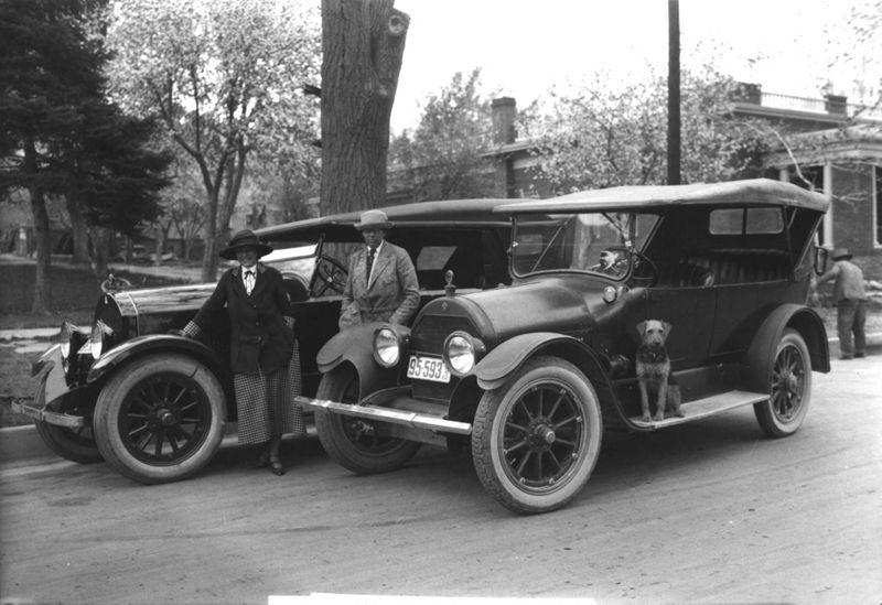 Black and white photo of Molloy and MacLeay standing next to cars
