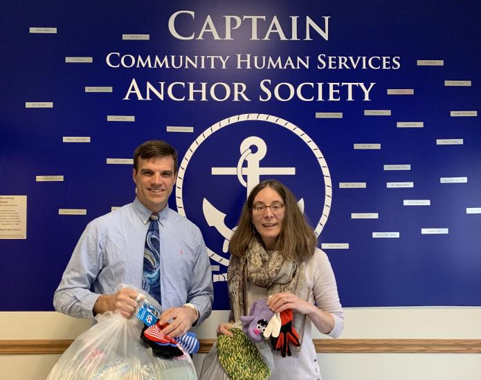 Woman and man holding bag of mittens and hats in front of Captain Community Human Resources Anchor Society sign