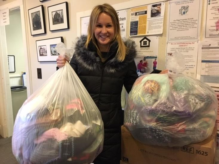 Woman holding two bags of donations