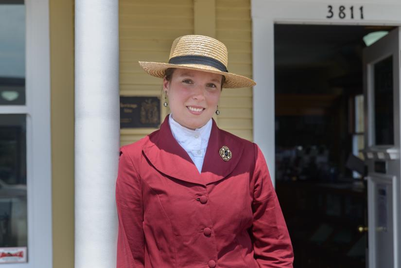 A costumed woman stands outside of the Steveston Museum.