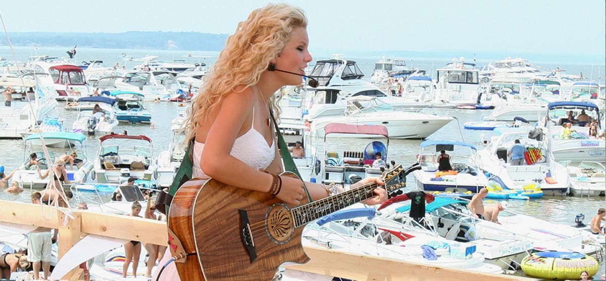 blonde woman holding a guitar and singing