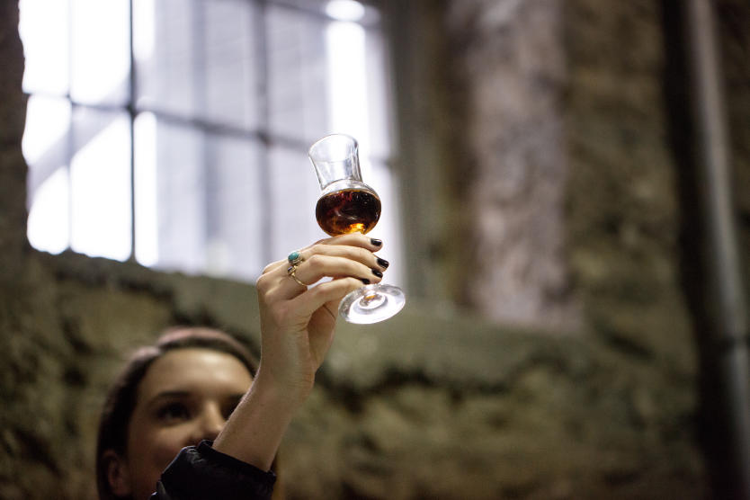 A woman holds a small tasting glass of bourbon up into the light from a window to view its color.