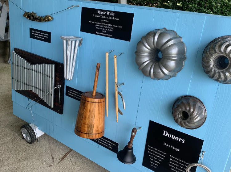 A blue board with historical musical instruments tacked on for display.