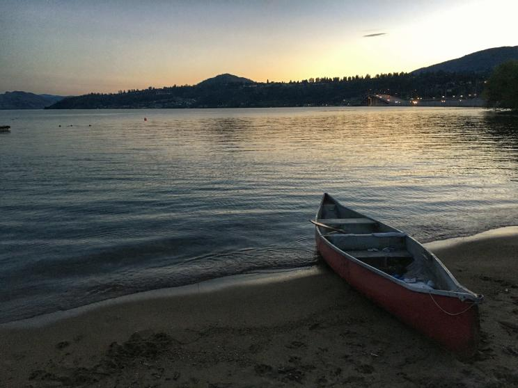 Canoe perched ashore while the sun sets on Okanagan Lake