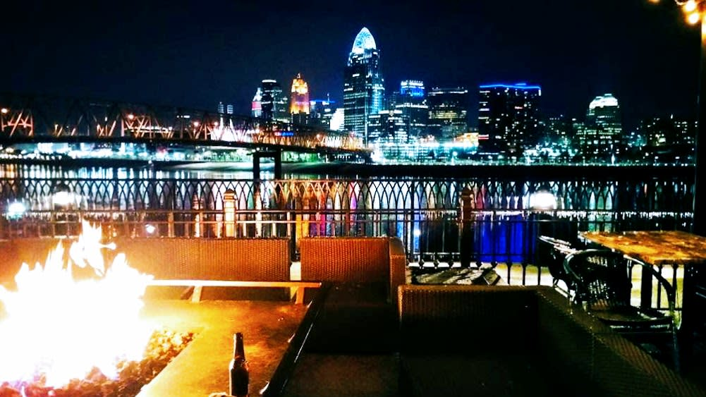 Fire burning on patio of Bar Louie with Cincy skyline in the background