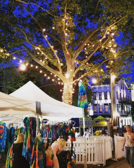 A tree strung with white lights shining down on colorful booths at a street festival in Mainstrasse Village