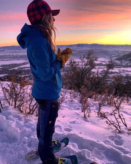 Woman watching the sun rise with a colorful sky in the background