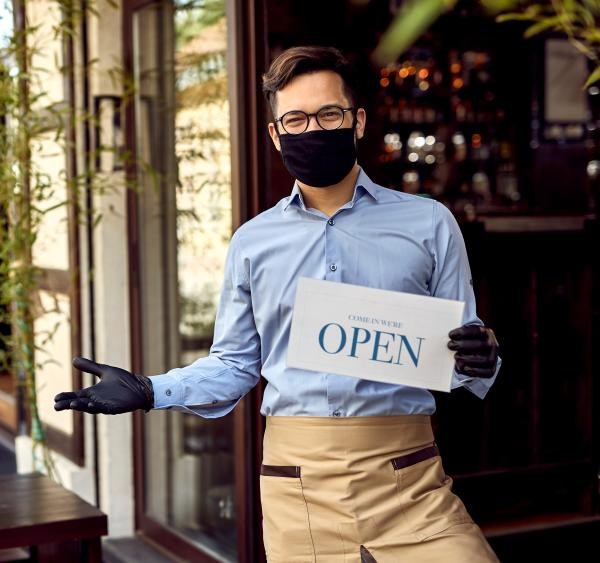 A server at a restaurant in downtown Irving reminds visitors that they are open.