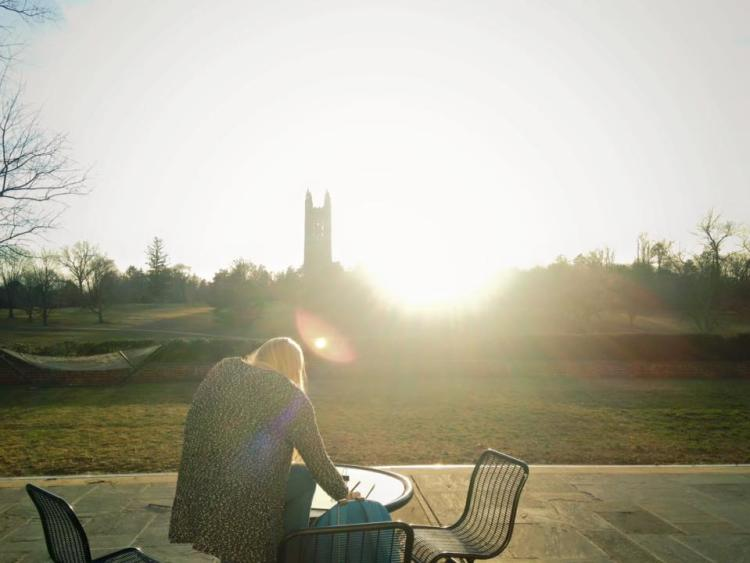 A young woman sits outside at a table with chairs and the Princeton University tower in the background