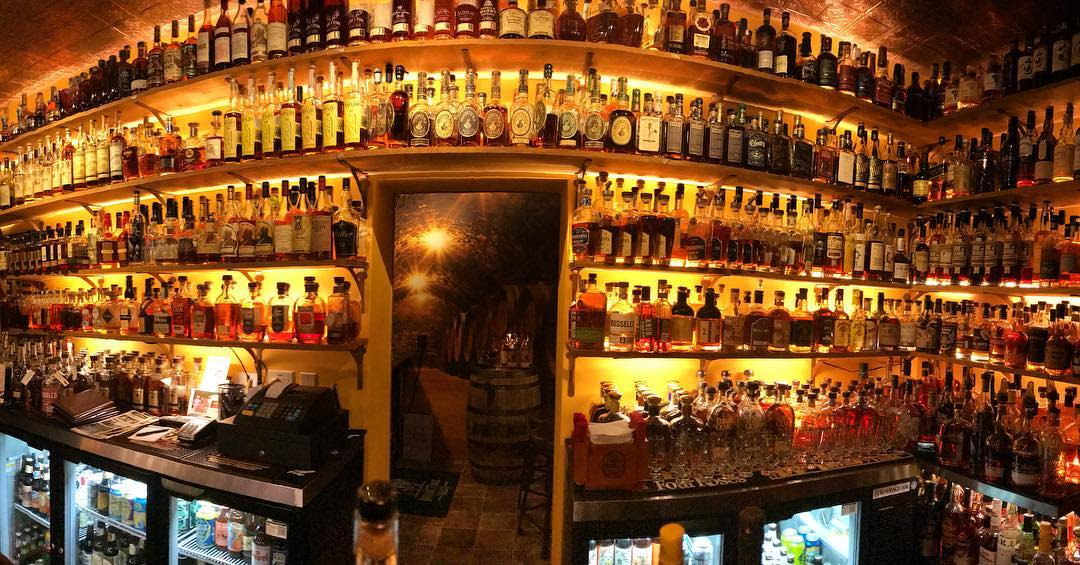A yellow-lit wall filled with more than 1500 bottles of bourbon