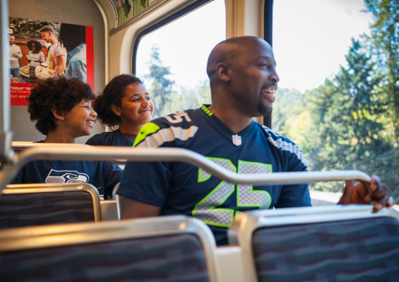 Father and Kids riding the light rail to a Seahawks game