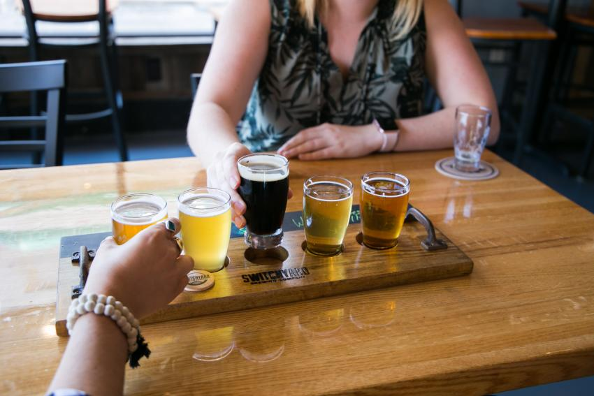 Two women enjoying a flight of beers at the Switchyard Brewing Co in Bloomington, IN.