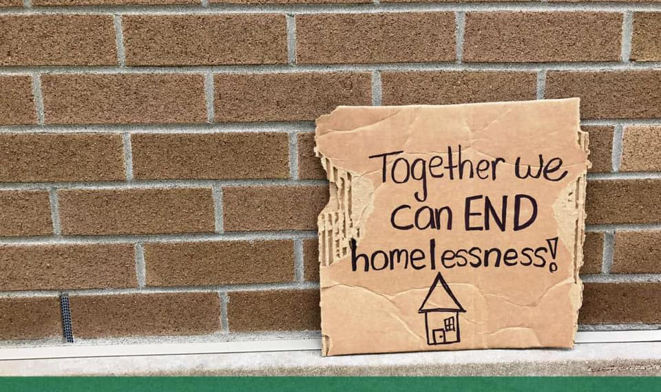 "Cardboard sign that reads ""together we can end homelessness!"" against brick wall"