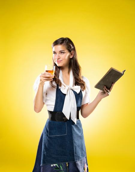 yellow background and woman holding a book in one hand and a bourbon glass in the other.  promotional for beauty and the bourbon tasting event.