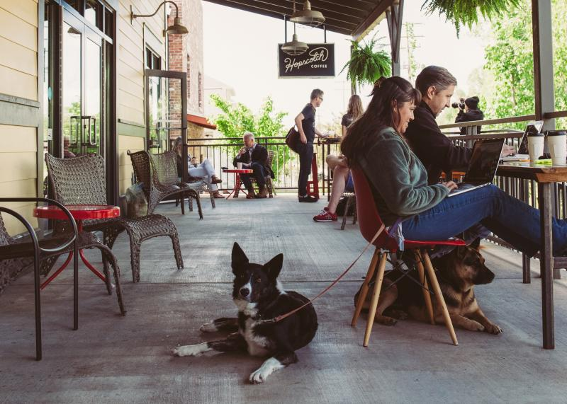People enjoying coffee with their dog on the patio at hopscotch in bloomington