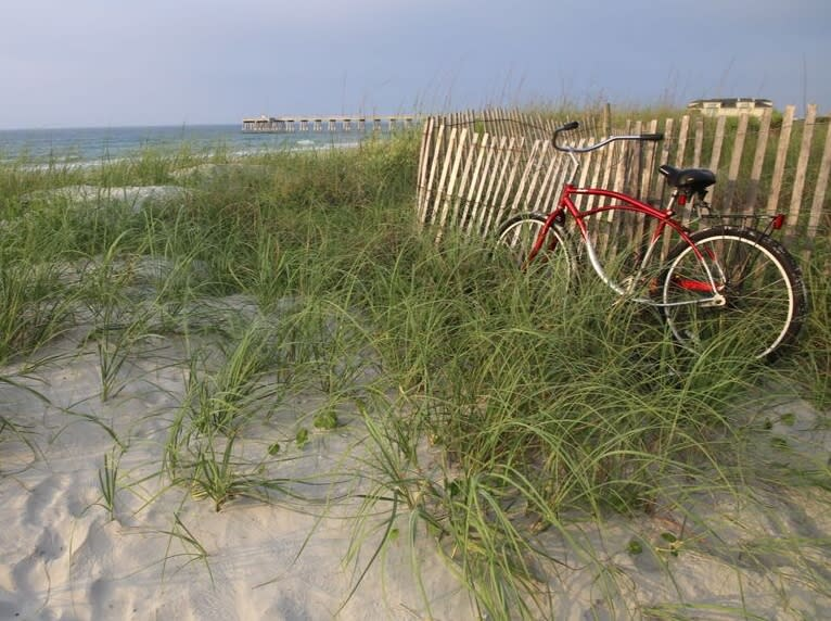 A bike resting against a fence on Wrightsville Beach, NC