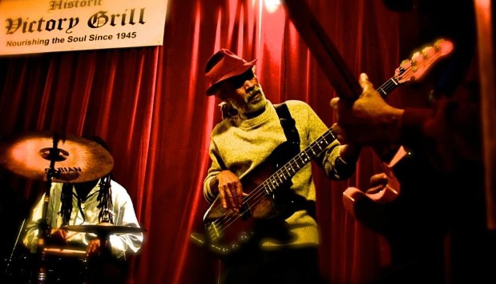 Harold McMillan playing guitar at Victory Grill