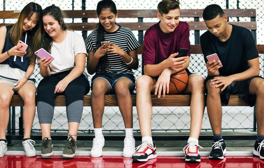 Teenagers texting on bench