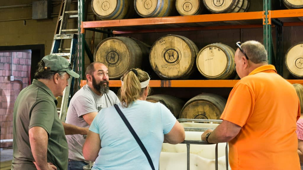 A tour guide at Barrel House Distilling Co. chats with patrons in a room full of bourbon barrels.