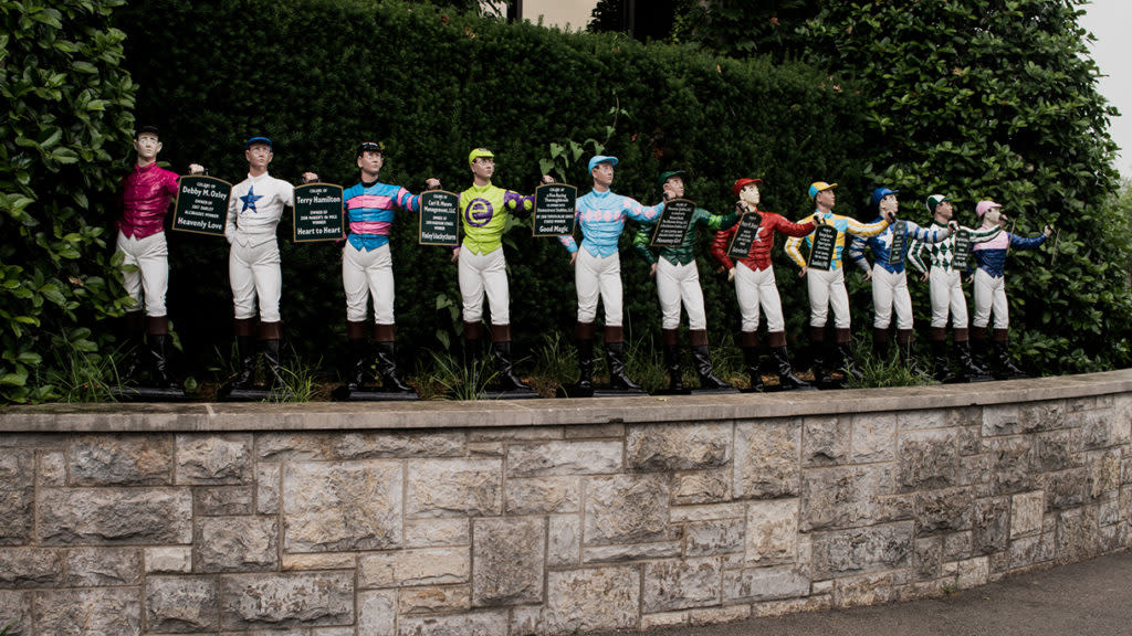 A line of medium sized jockey statues in a row at Keeneland's Jockey Garden.