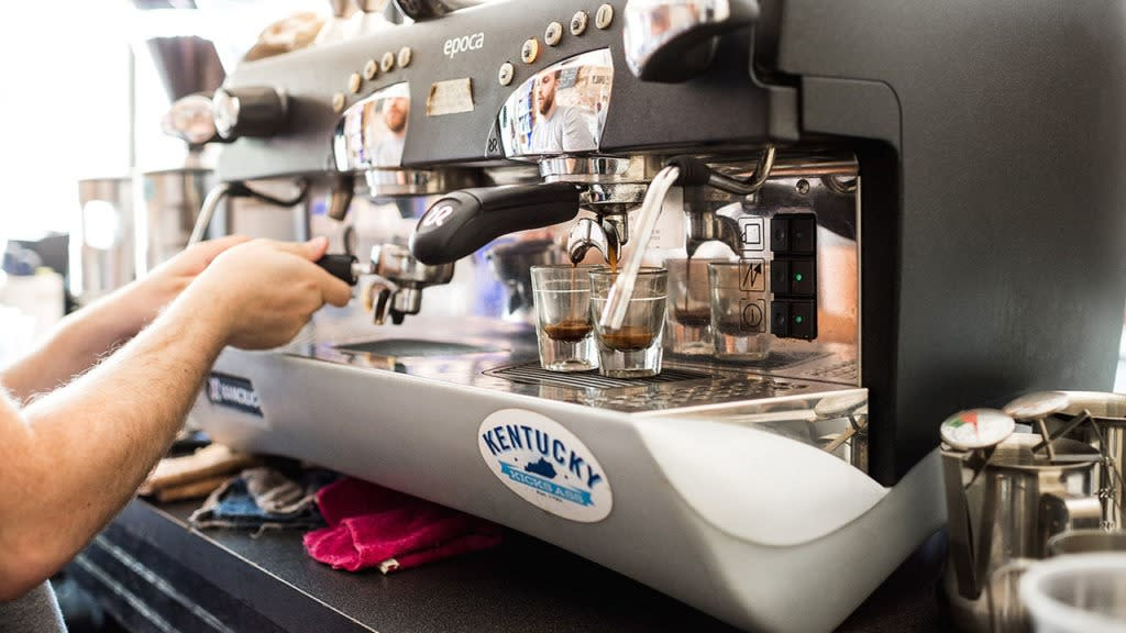 A part of hands using an espresso machine