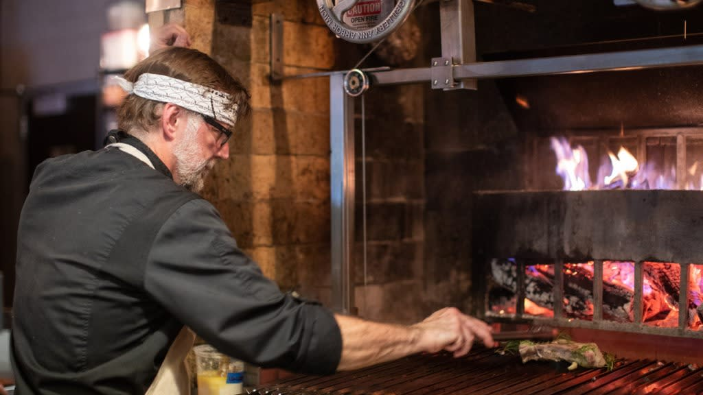 A chef grills a piece of meat at Middle Fork Kitchen Bar.