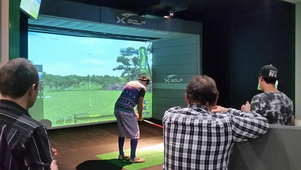 Friends watch as man tees up indoors at X-Golf in Lafayette, LA