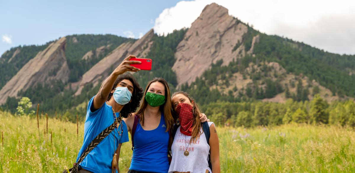 Group taking a selfie in front of the Flatirons