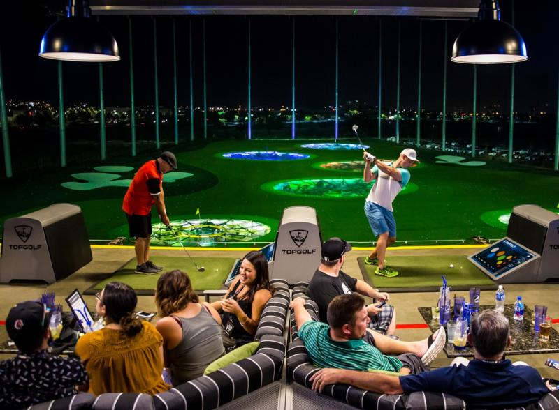 Group of friends lounging on couches and hitting golf balls in hitting bay at Topgolf
