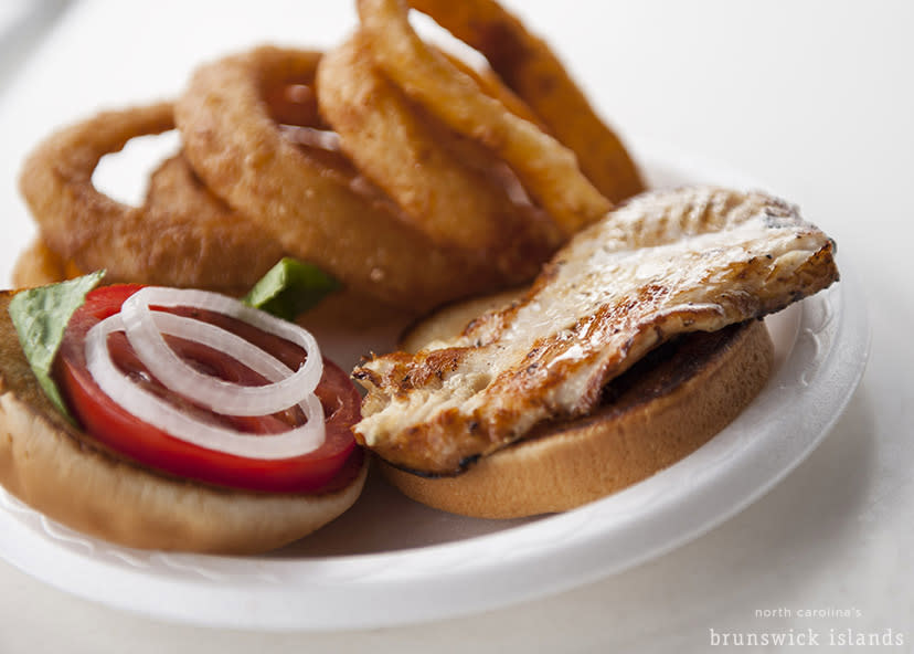 A fresh sandwich paired with onion rings from a local eatery makes perfect picnic fare.