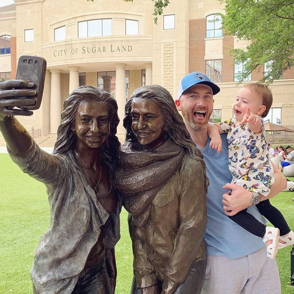 Dad and daughter next the selfie statue