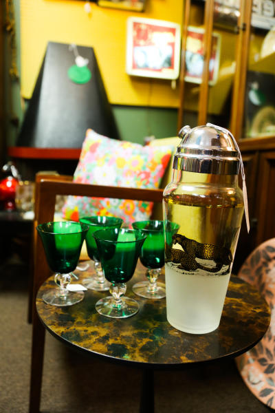 Green glassware and a cocktail shaker with a leopard illustration are on display at Salt City Antiques in Ypsilanti
