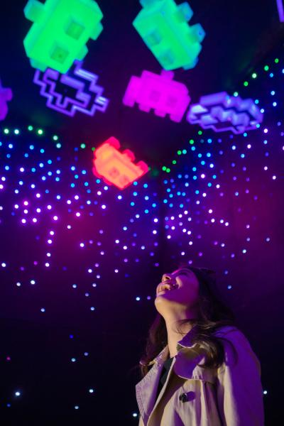Woman looking up admiring colorful LED Space Invaders inside Otherworld exhibit