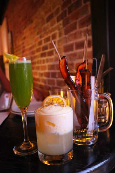 Green drink in champagne flute with lemon, vodka cocktail with cream and lemon and empty glass with bacon