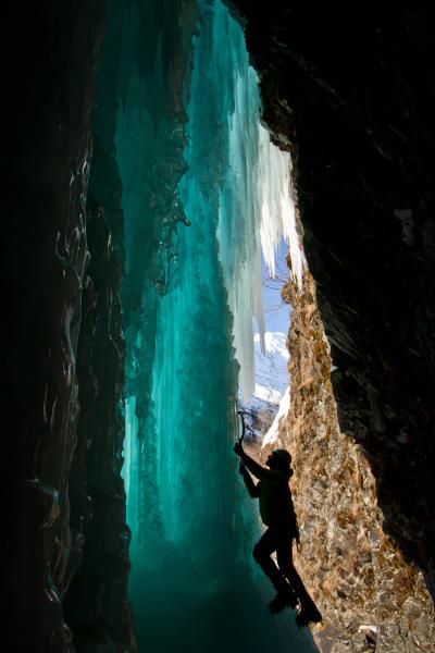 an ice climber on a frozen waterfall