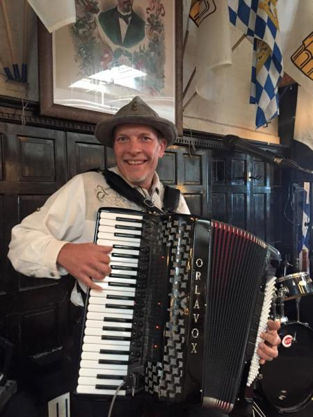 man playing accordion with smile on his face at hofbrauhaus in newport ky