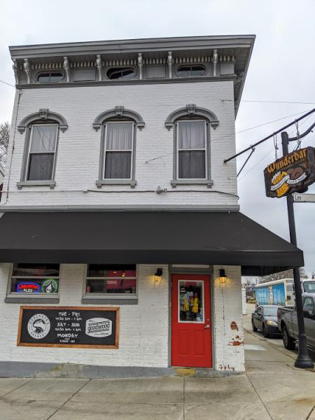 exterior shot of a white building with black awning and red door with sign showing wunderbar in covington kentucky