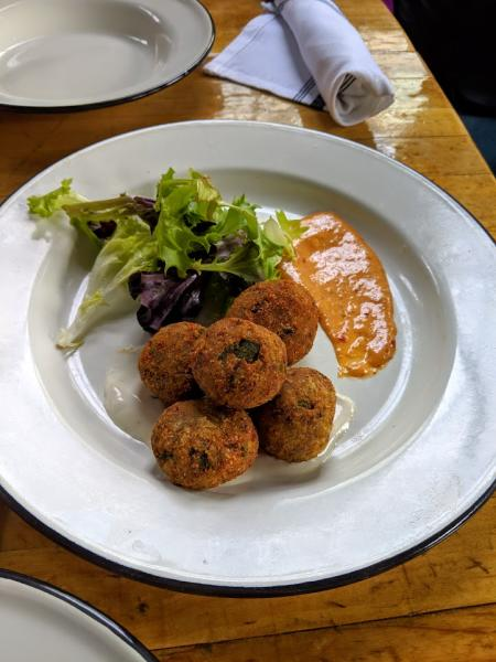 goetta hush puppies from libbys southern comfort in covington ky with green garnish and sauce on the side of a white plate