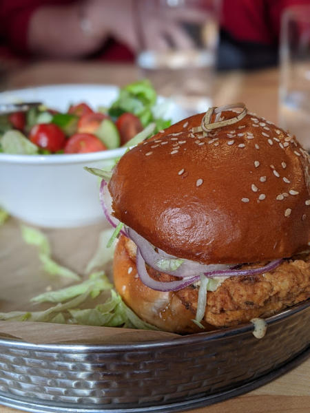 up close shot of a chicken sandwich on sesame seed bun at the kitchen by butlers pantry in covington kentucky