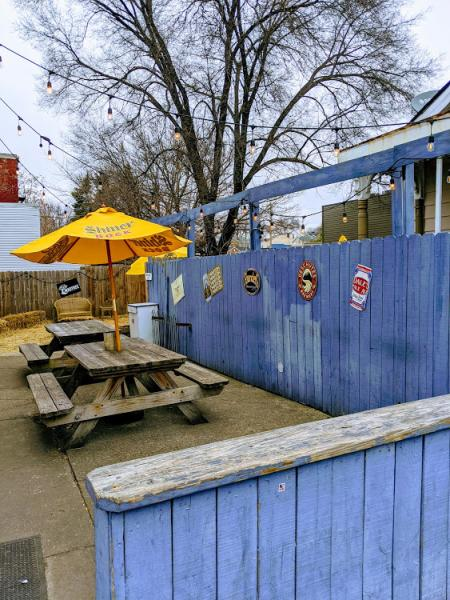photo of a blue wooden fence and yellow patio umbrellas with picnic tables at the wunderbar in covingtin ky