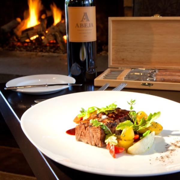 Plated Venison Dish with Veggies and Bottle of Wine in Front of Fire at Copperleaf