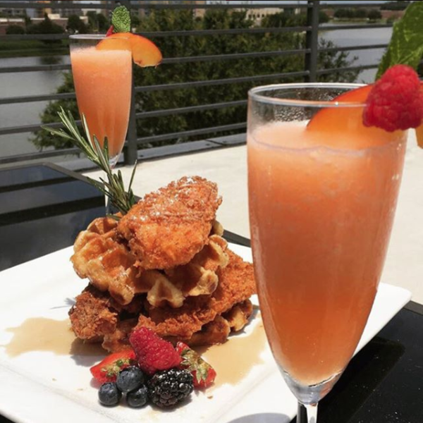 The Roof's Chicken & Waffles served with a side of berries and enjoyed with a couple of mimosas.