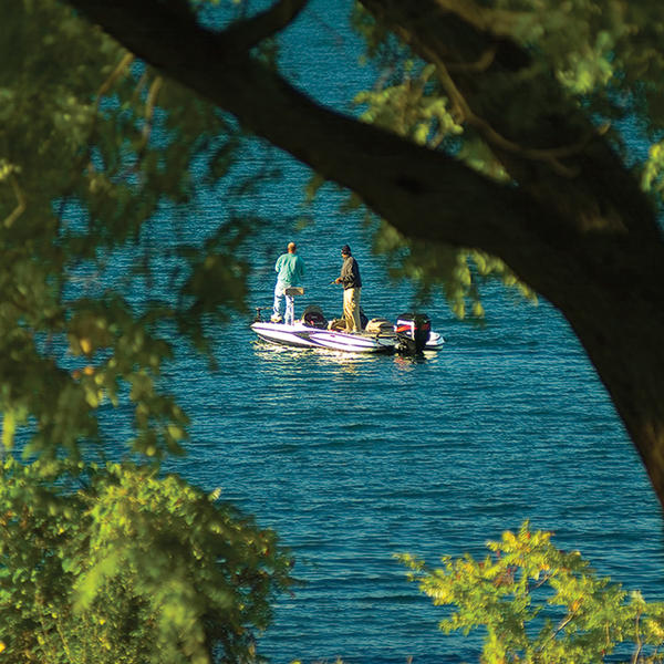 Two people fishing off a boat on Owasco Lake in Auburn New York.
