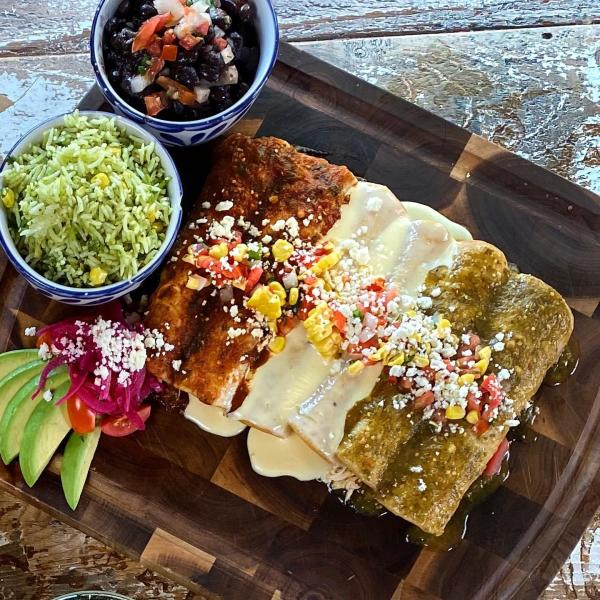 A plate of enchiladas from Mexican Sugar come with red, white, or green sauce and a side of rice & beans.
