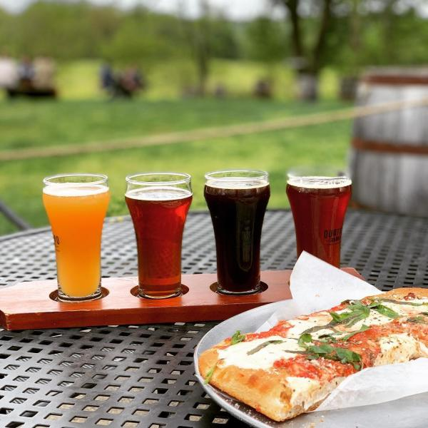 Quattro Goomba's beer flight with pizza slice
