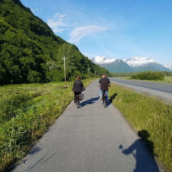 a couple rides bikes on a scenic bike path