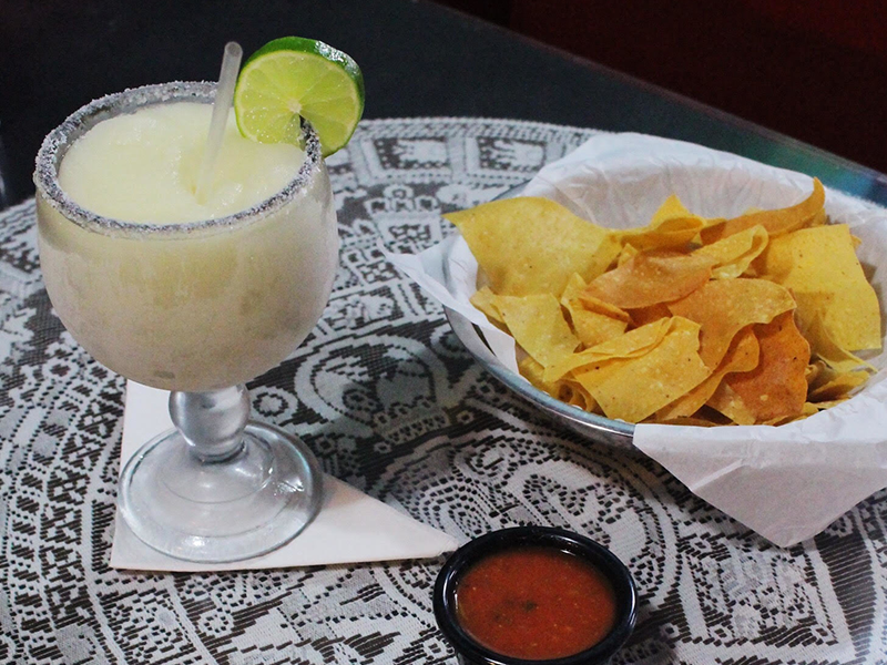 A frozen margarita from Arturo's is served in a salted glass with lime and fresh tortilla chips.