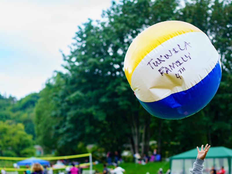 "beach ball with ""Tukwila Family 4th"" written on it soaring above families at park"